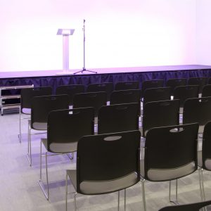 Rows of empty black chairs looking towards a stage and microphone